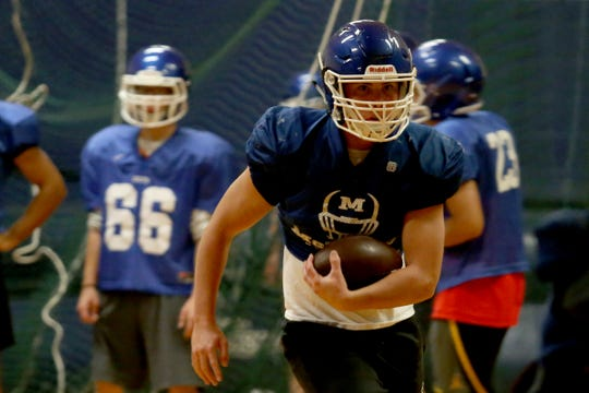 Junior Walling practices with the McNary football team inside as wildfire smoke lingers over the Willamette Valley at McNary High School in Keizer on Wednesday, Aug. 22, 2018.