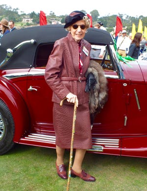 Angela Cantore of Oak Brook, Ill. poses with her 1935 Mercedes Benz 540K Cabriolet A during the 68th Annual Pebble Beach Concours d'Elegance held Sunday. Mrs. Cantore, who has attended the Concours annually for 36 years, commissioned a Chicago designer to construct a dark cherry ostrich skin leather suit to complement her Mercedes Benz when displayed on the 18th fairway. She is holding her mother-in-law's silver fox stole and uses it to ward off the chill morning breeze.