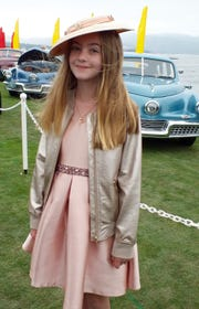 Alex Tremulis, 11, of the Bay Area, poses in front of a row of Tucker automobiles designed by her great uncle Ales Tremulis. A dozen Tuckers were on display in the featured class during the 68th Annual Pebble Beach Concours d'Elegance held Sunday. Tremulis is wearing a rose gold dress she recycled from her fifth grade graduation and a vintage hat she selected for the occasion.