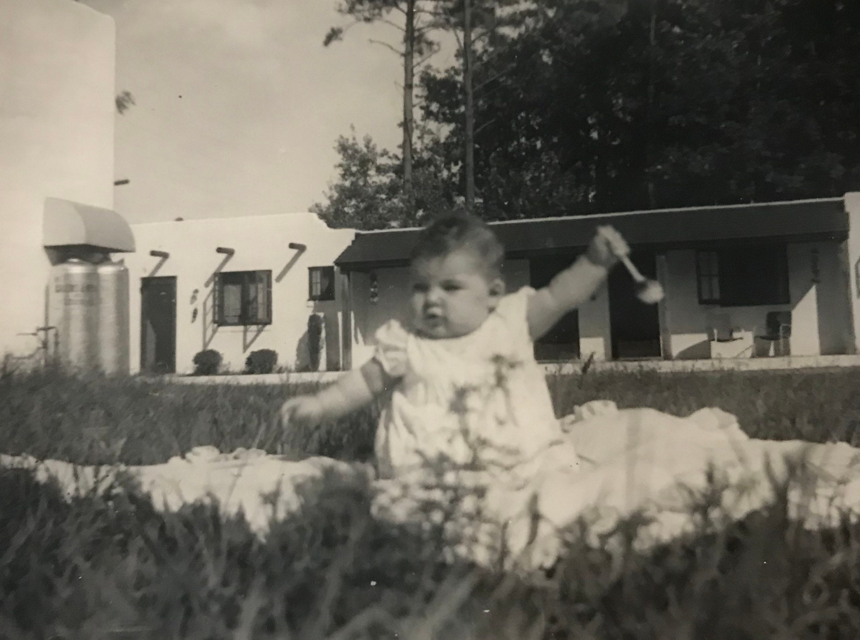 Sue Jones, whose great uncle was the founder Bill Weaver, plays in the grass outside of the Alamo Court in West Ocean City