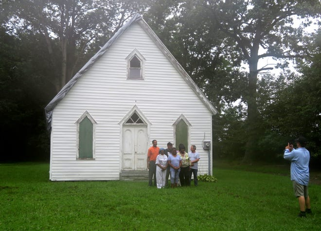 John Muller snaps a photo of a group of community members standing outside historic Bazzel Church.