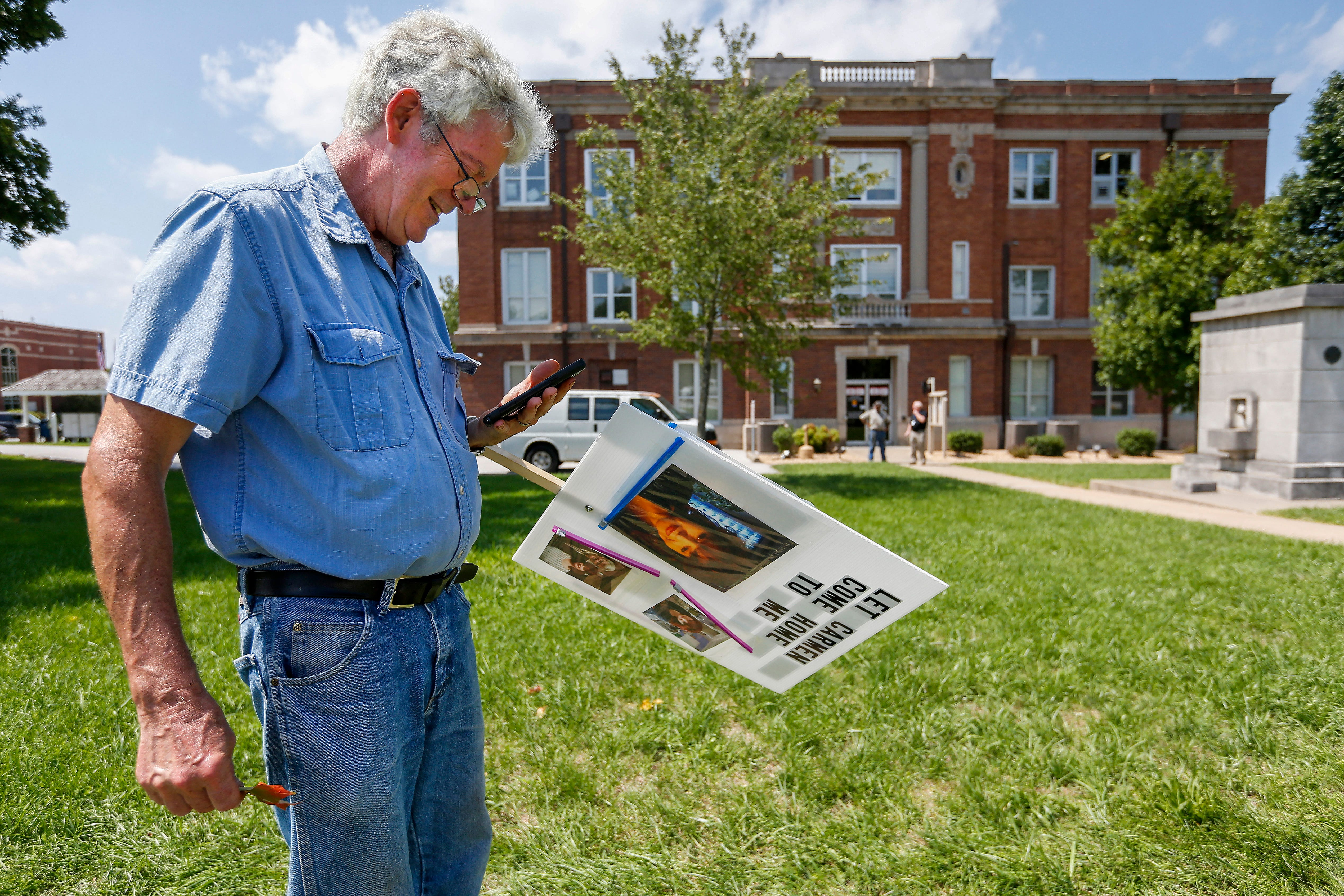 Stuart Foraker talks to his wife Carmen Foraker on the phone while protesting in front of the Christian County Historic Courthouse on Monday, Aug. 27, 2018. Carmen is stuck in Romania because she can't renew her passport.