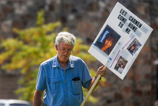 Stuart Foraker walks in front of the Christian County Historic Courthouse on Monday, Aug. 27, 2018 holding up a sign with pictures of his wife Carmen Foraker on them. Carmen is stuck in Romania because she can't renew her passport.