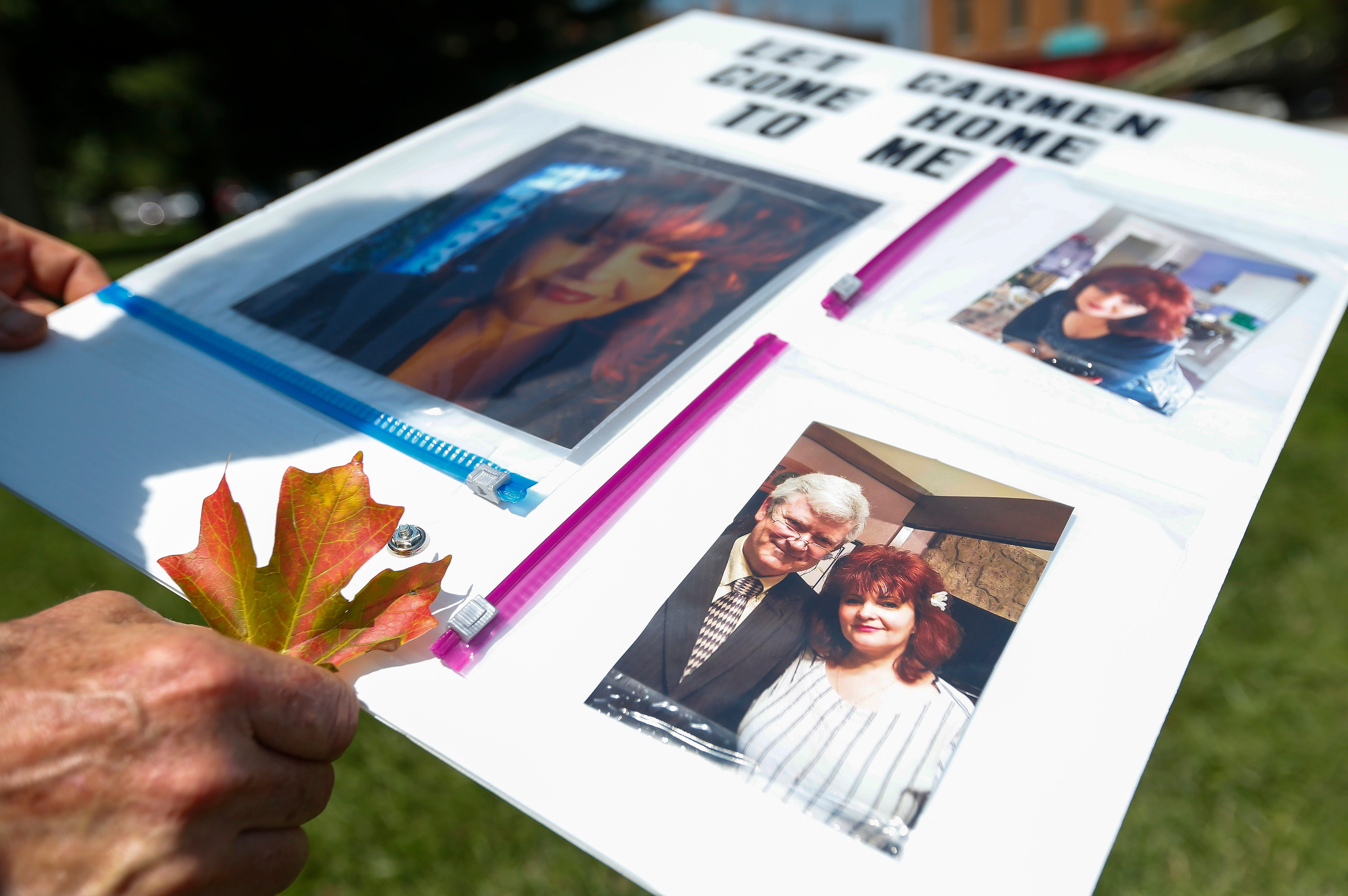 Stuart Foraker holds a sign with pictures of his wife Carmen Foraker on them including a photo from their wedding day at bottom right. Carmen is stuck in Romania because she can't renew her passport.