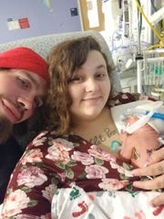 "Photographed at University of Virginia Health System University Hospital, Staunton's Cassandra Brooks and Brandon Pritt hold their newborn infant Raven Diana Ivy Pritt, who was born Aug. 8. ""Our first family photo,"" says Brooks. Raven was born with Generalized Arterial Calcification of Infancy (GACI), a rare genetic disease that affects 1 in 391,000 babies."