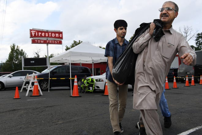 Fahad Ibrahim helps his father, Muhammad Ibrahim, carry a garbage bag of meat from Lebanese Butchers Slaughterhouse. City officials had said that the slaughterhouse would not be granted the special event permit they were required to have to accommodate their hundreds of expected customers.