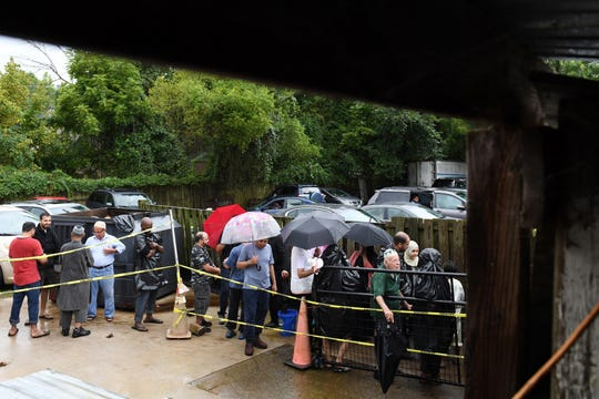 Customers wait in the rain at Lebanese Butchers to get meat. Town officials relented and said the slaughterhouse would be able to proceed with its holiday operations as planned, but they said zoning concerns persist.