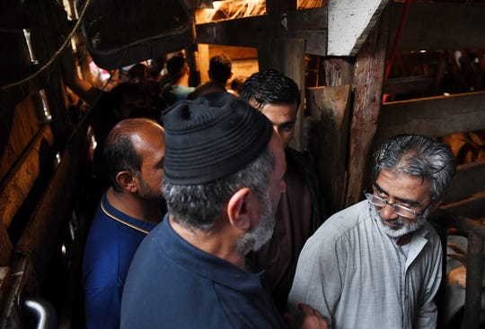 People wait to pick out an animal at Lebanese Butchers Slaughterhouse for Eid al-Adha, a holiday commemorating the prophet Ibrahim's willingness to sacrifice his son Ismail at God's behest, and God's ultimate decision to let Ibrahim slay a sheep instead. MUST