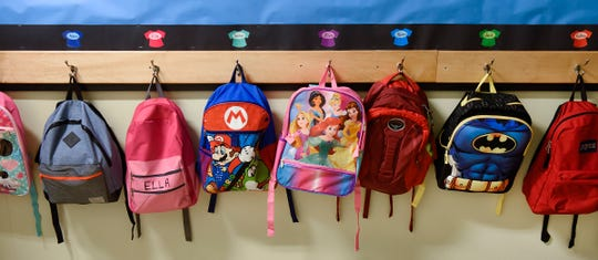 Students backpacks hang on hooks in the hallway at All Saints Academy Monday, Aug. 27, in St. Cloud.