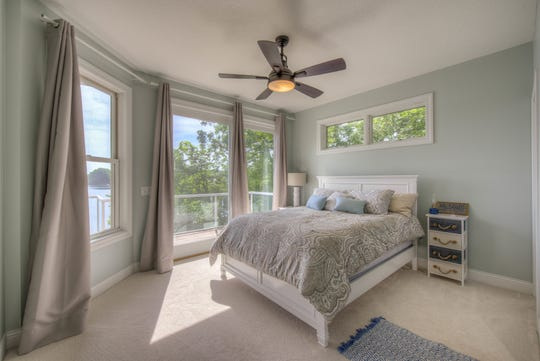 The master bedroom includes floor-to-ceiling windows as well as an above-bed transom to let in soft, natural light.