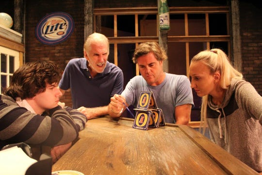 "Brendan Wenger (Adam,left ), Steve Budkiewicz (Ray) and Chelsea Wenger (Janet, right) watch intently as Jason Miles (Palmer, center) demonstrates how Building 7 was imploded on 9/11, falling like a house of cards. All are in Vero Beach Theatre Guild's ""Yankee Tavern."""