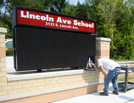 Bruce Custer, a fiber optic sign technician, works on the sign outside Vineland's Lincoln Avenue School on Monday, August 27.