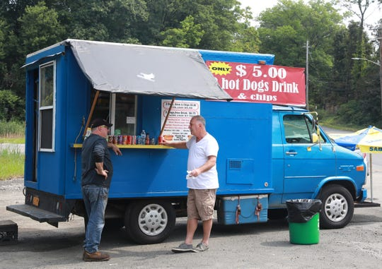People wait for their orders at the food truck on Old Nyack Turnpike in Nanuet on Aug. 27, 2018. A great place to get a cheap lunch on the run for only $5 with 2 hot dogs, chips and drink.