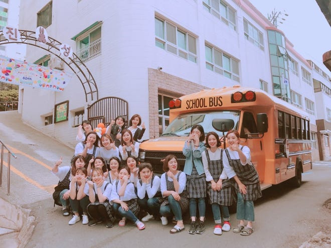 South Korean students pose in front of one of New York-based Trans Tech's buses. The bus is the first ever American-made school bus in the country.