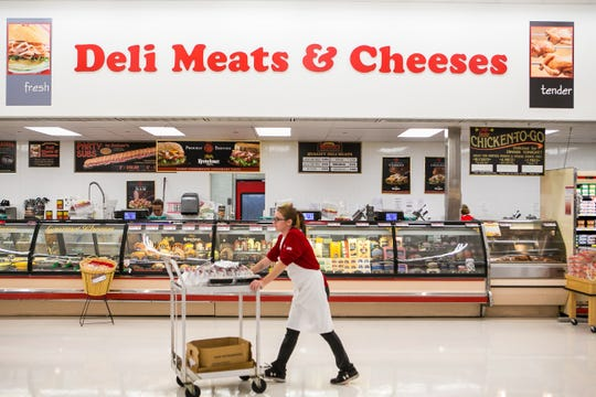Deli clerk Amber Owens walks by the deli section at Redner's Warehouse Markets at the Shoppes at Fieldstone shopping center north of Dover.