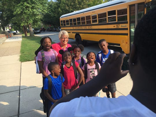 Vincent Rollins takes a picture of his kids, nieces and nephews with Highlands Elementary School Principal Barbara Land on the first day of school Monday.