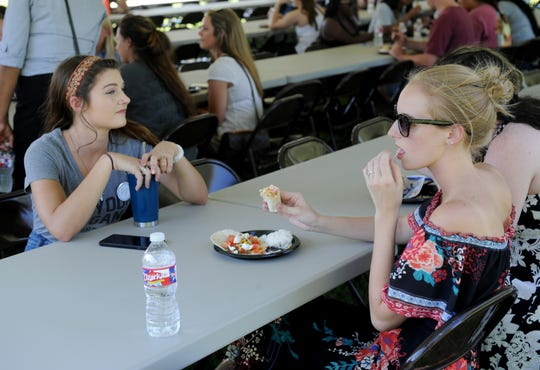 Brenna Rhodes, left, Courtney Lawrence and Ayesha Parr have dinner at Midwestern State University's President's Picnic Monday, Aug. 27, 2018, on the lawn of the Sikes House president's mansion.