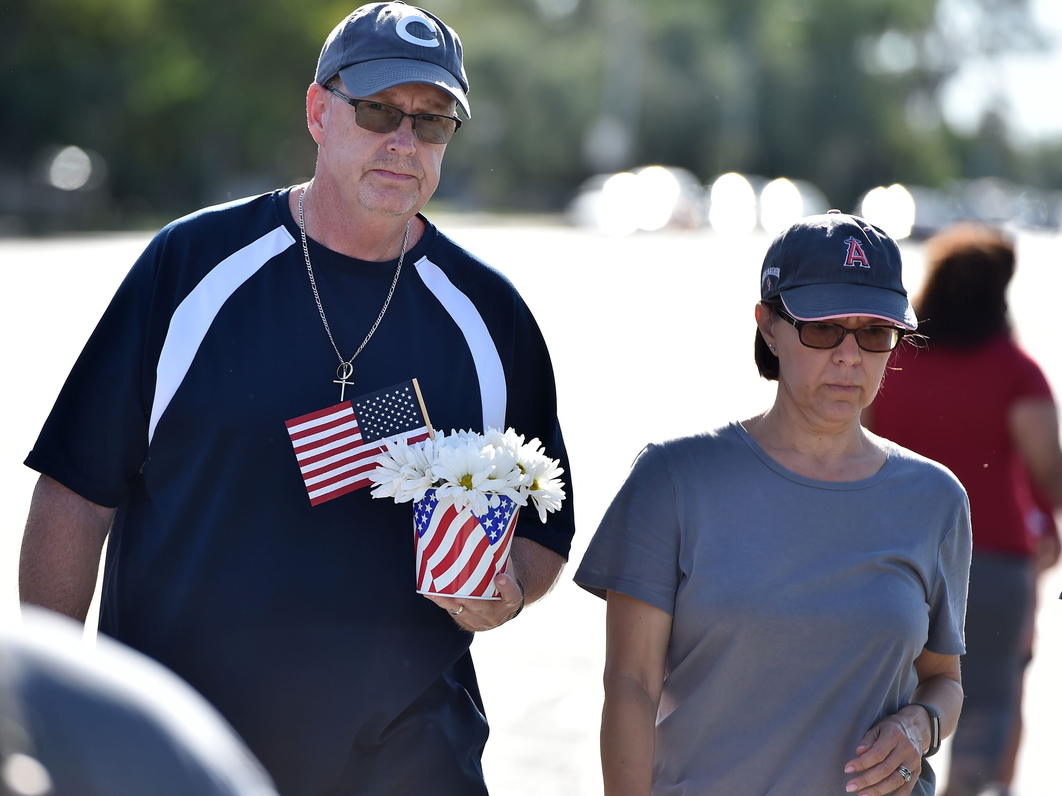 Tim Combs carries flowers to pay respect to US Senator John McCain, outside a mortuary home in Phoenix, Arizona, August 26, 2018. - McCain, who died on August 25 at age 81, will lie in state in the Capitol Rotunda in Phoenix and receive a full dress funeral service at the Washington National Cathedral. (Photo by Robyn Beck / AFP)ROBYN BECK/AFP/Getty Images ORG XMIT: Veteran U ORIG FILE ID: AFP_18M6F6