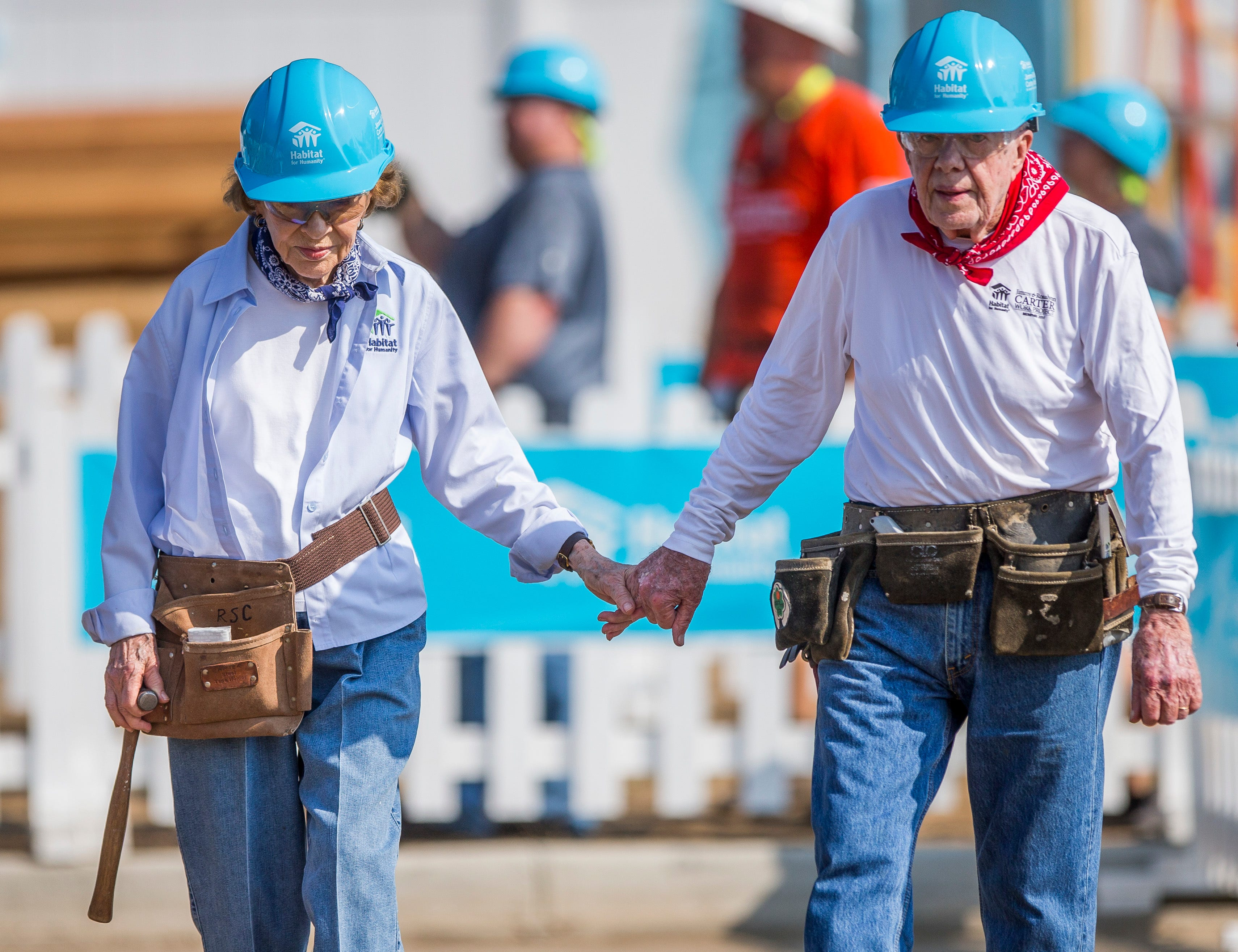 Former President Jimmy Carter holds hands with his wife, former first lady Rosalynn Carter, as they work with other volunteers on site during the first day of the weeklong Jimmy & Rosalynn Carter Work Project, their 35th work project with Habitat for Humanity, on Monday, Aug. 27, 2018, in Mishawaka, Ind.