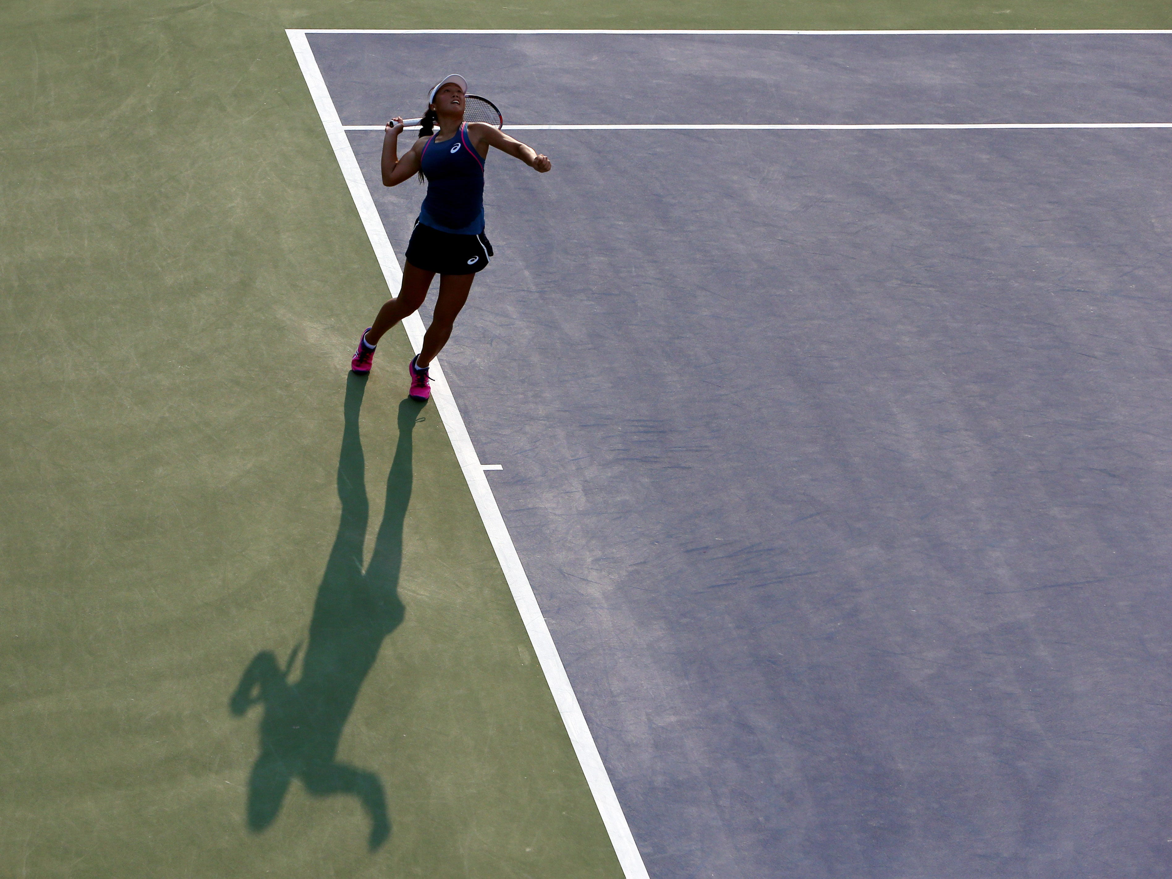 The shadows, and evening, arrive as Claire Liu of the USA serves  to Polona Hercog of Slovenia. Liu won  7-6 (4), 1-6, 6-4.