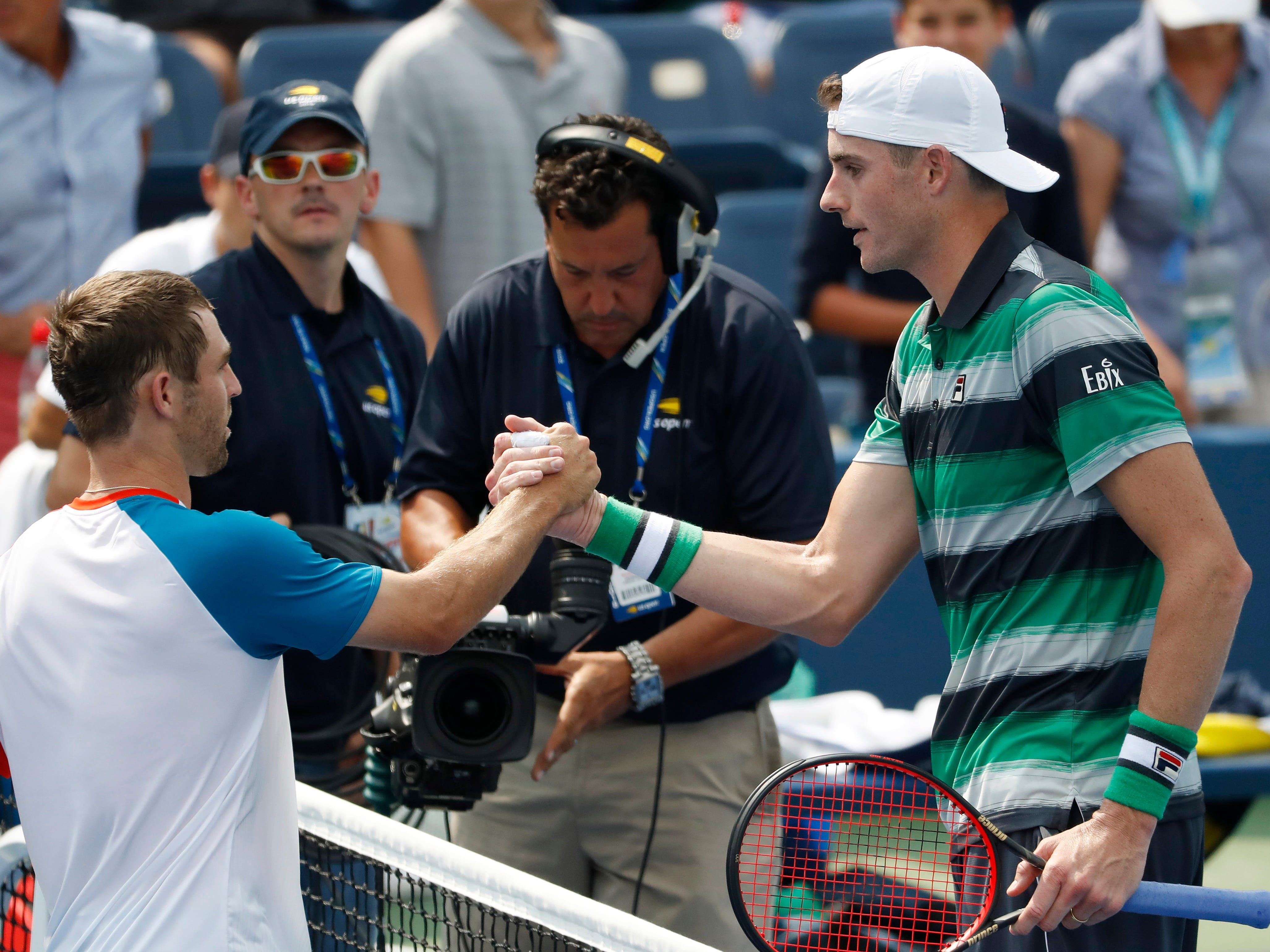 John Isner (right) shakes hands with fellow American Bradley Klahn. Isner won 7-6 (3), 6-3, 6-4.