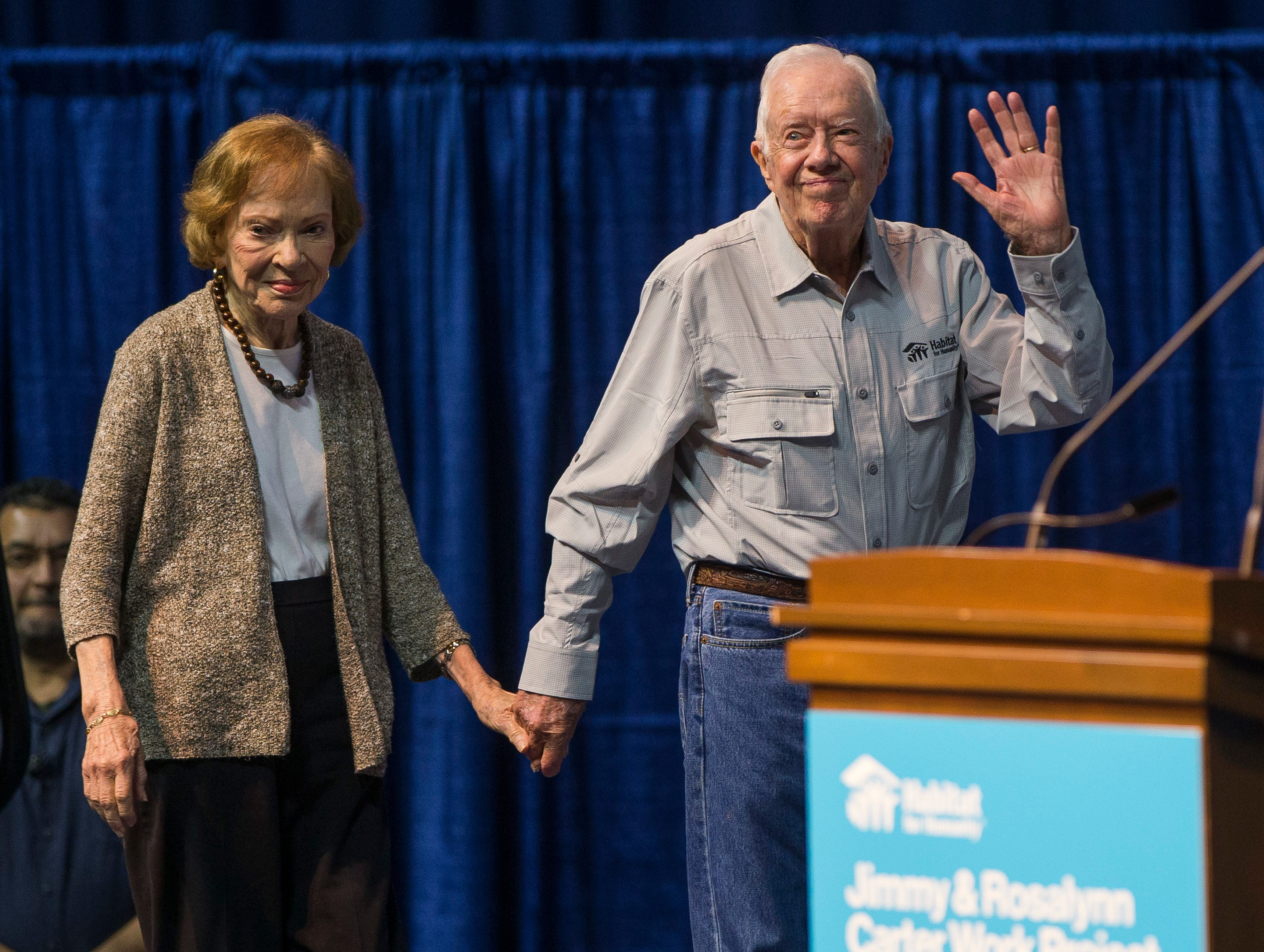 Former President Jimmy Carter waves to the crowd as he takes the stage with his wife, former first lady Rosalynn Carter, during the opening ceremony for the Jimmy & Rosalynn Carter Work Project, Sunday, Aug. 26, 2018, inside the University of Notre Dame's Purcell Pavilion in South Bend, Ind.