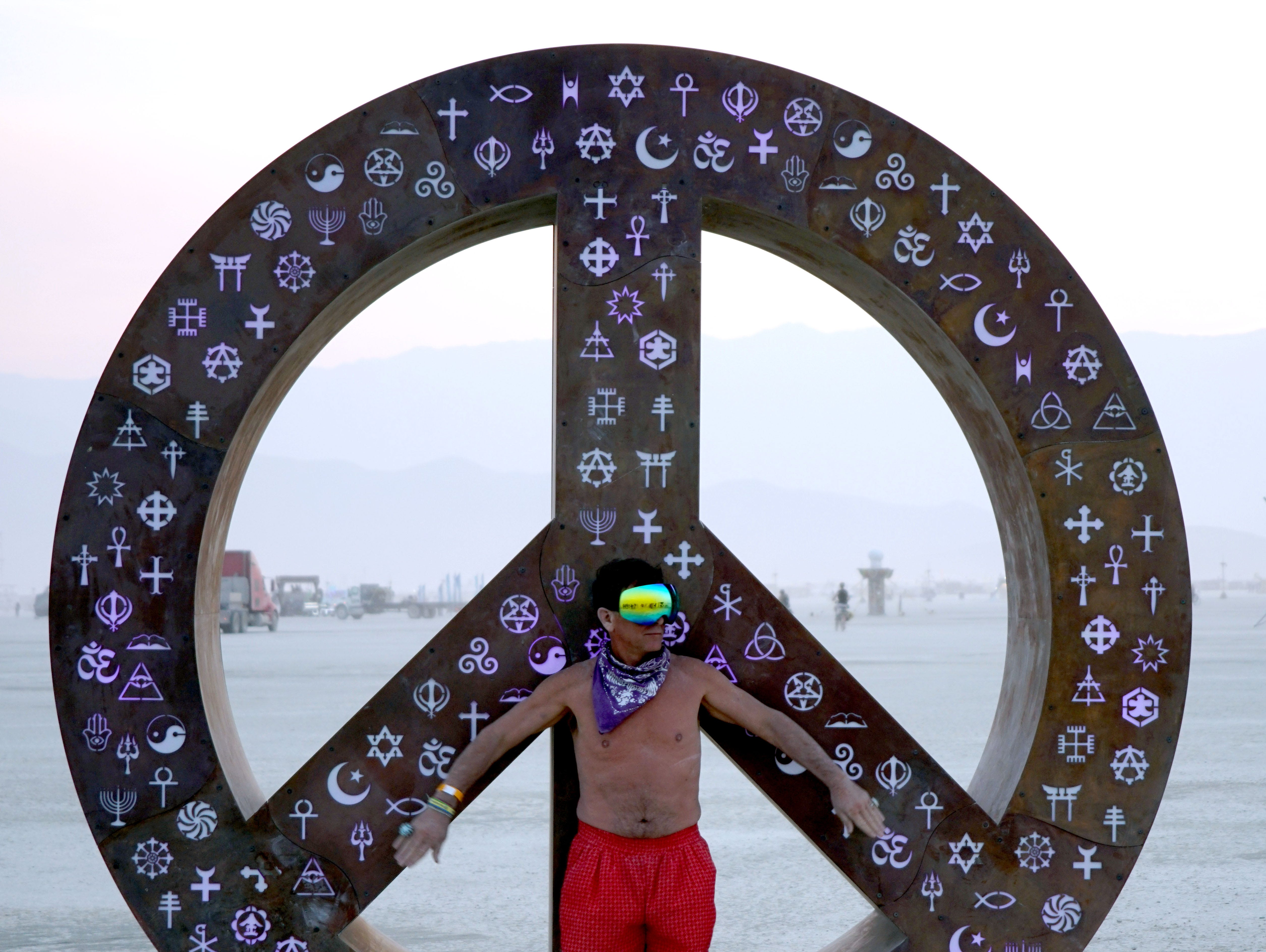 "Shane Spring of Toronto poses with the sculpture ""Symbolic Peace"" by Mathew Rosenblatt of Toronto that he helped build and install at Burning Man."