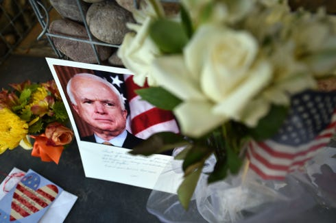 Photographs, flowers and notes gather at a makeshift memorial to Sen. John McCain outside his office in Phoenix, on Aug. 26, 2018.