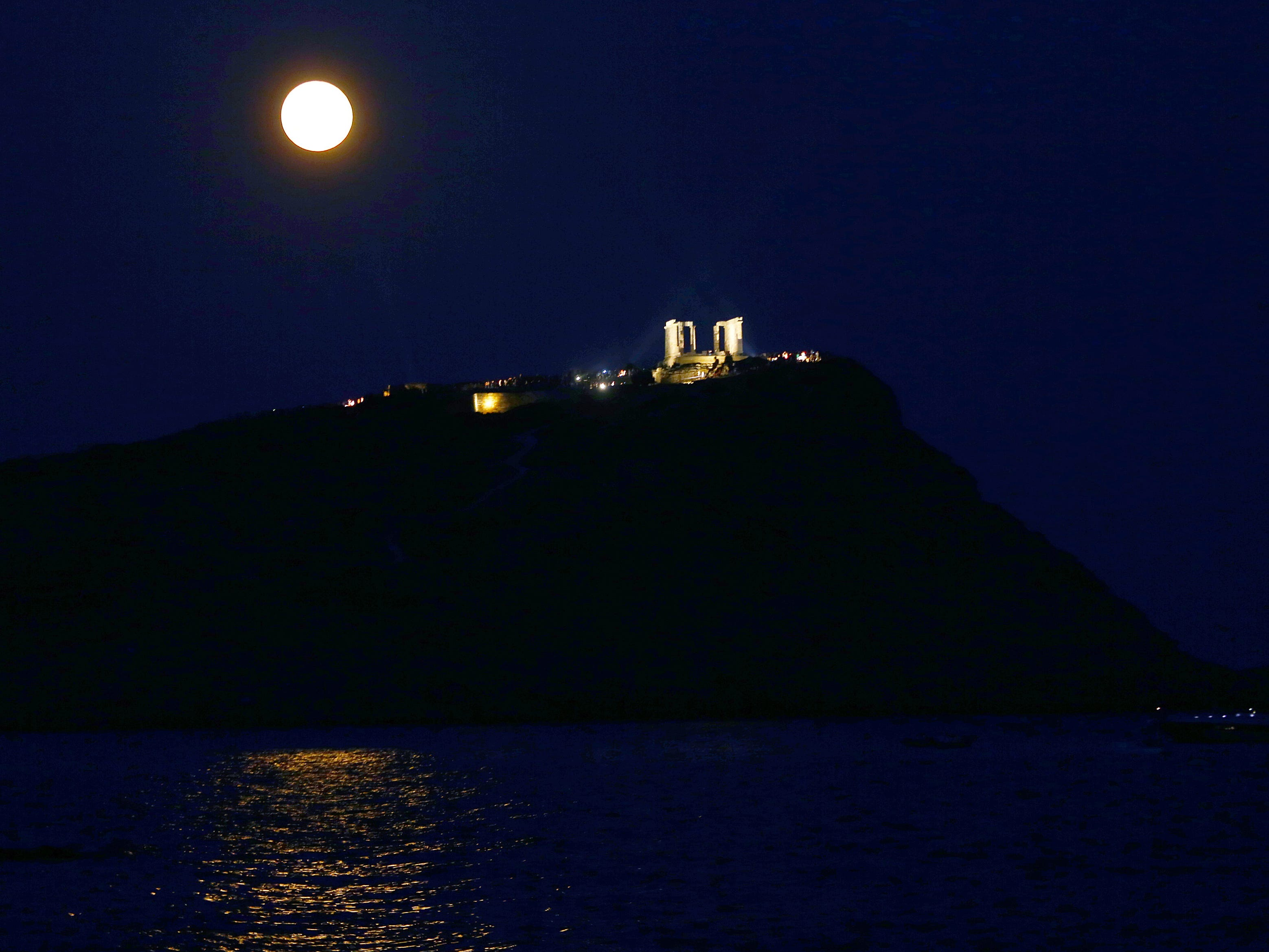 The full moon rises over the ancient temple of Poseidon, on Cape Sounio, Greece, Aug. 26, 2018.