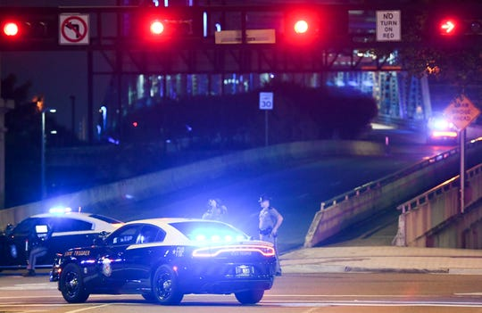 """Police vehicles block one of the bridges leading to the Jacksonville Landing, where a gunman killed two people and wounded several at a """"Madden 19"""" tournament before fatally shooting himself."""