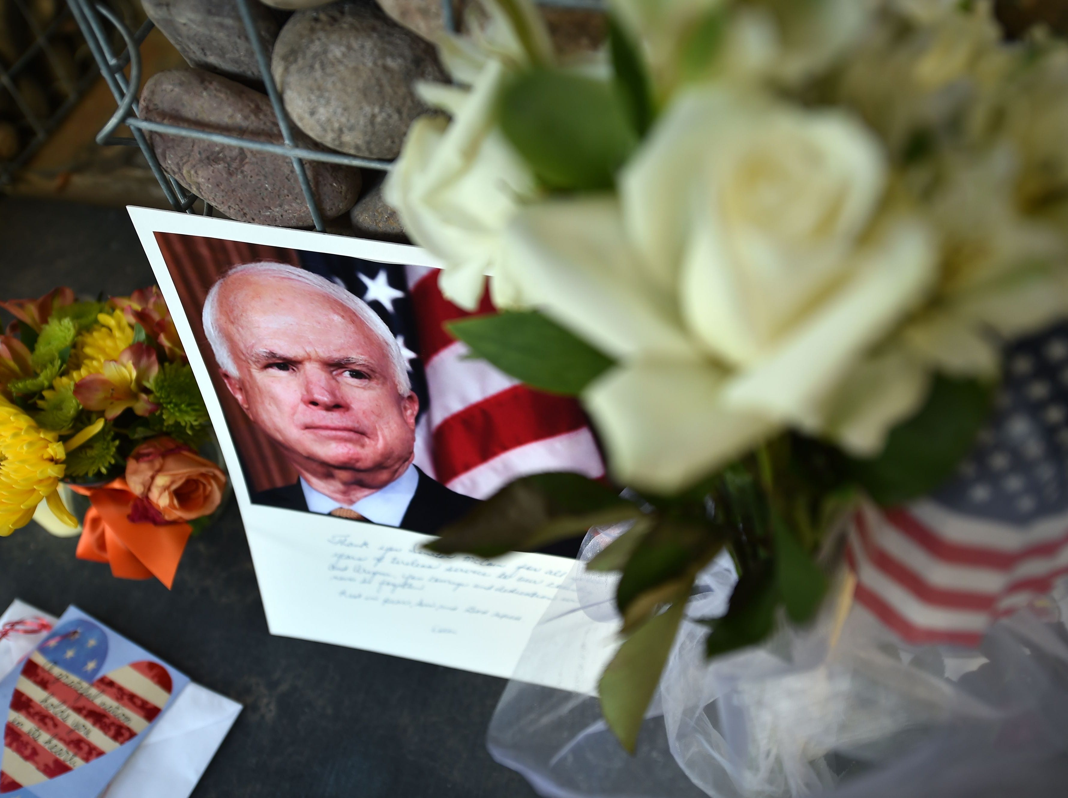 Photographs, flowers and notes gather at a makeshift memorial to US Senator John McCain outside his office in Phoenix, Ariz. on Aug. 26, 2018.