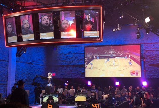 Heat Check Gaming players are seen on the screens above their seats while action from their game against Knicks Gaming is shown on another screen, Saturday, Aug. 25, 2018, in New York.