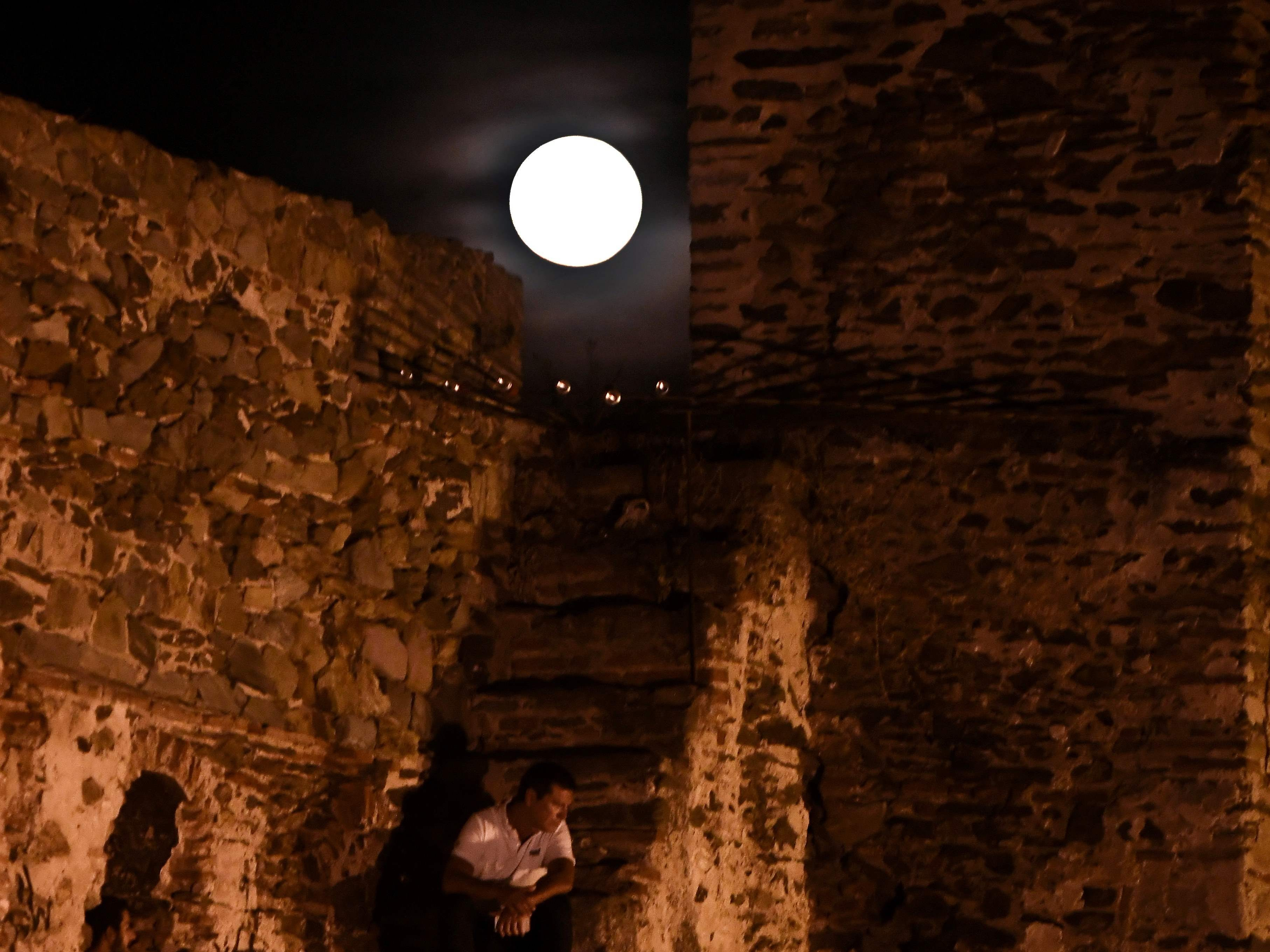 People watch a musical event under the full moon on the Byzantine Walls in Thessaloniki on Aug. 26, 2018 in Thessaloniki, Greece.