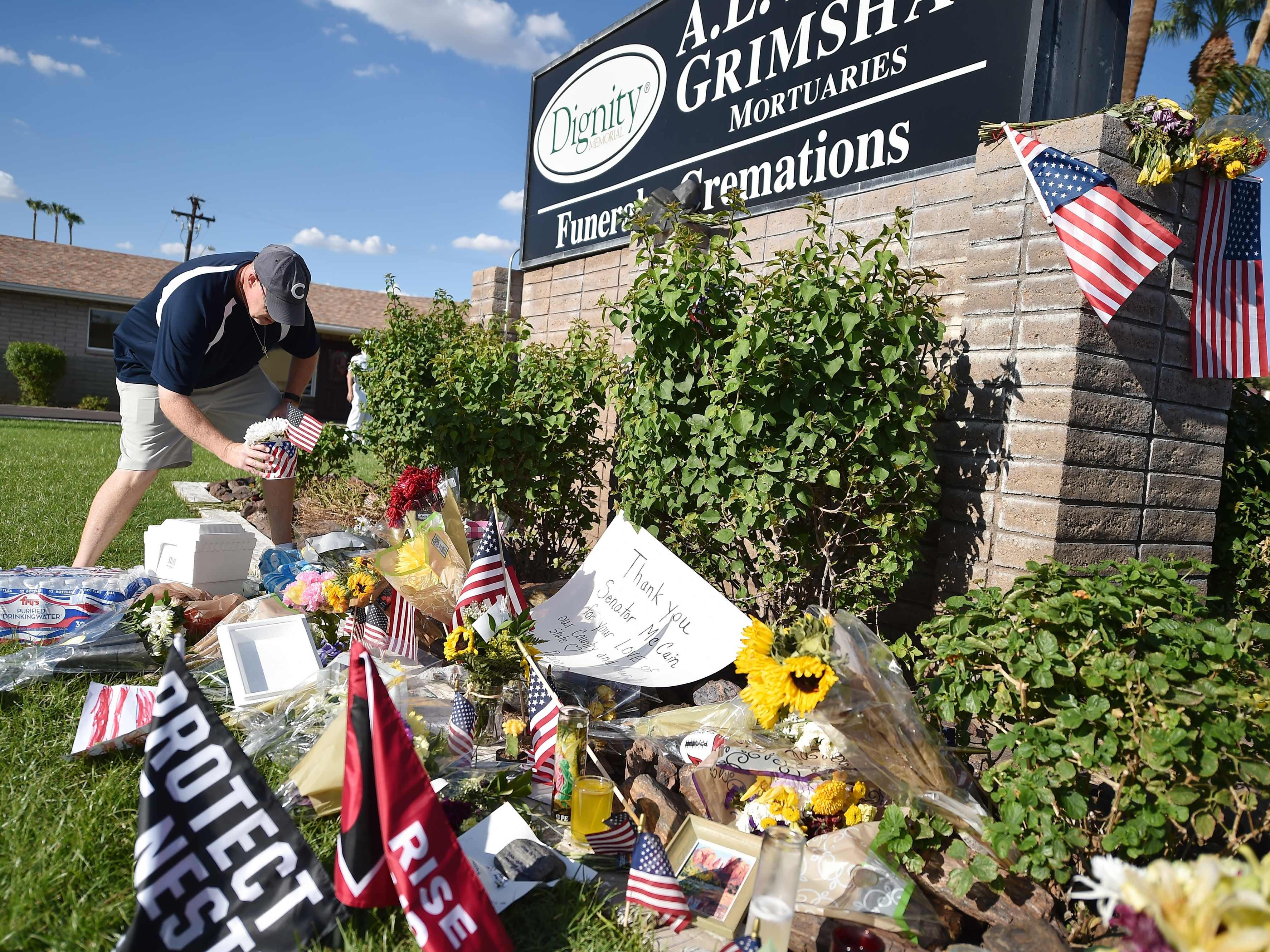 Tim Combs leaves flowers at a makeshift memorial for US Senator John McCain, outside a mortuary home in Phoenix, Arizona, on August 26, 2018. - McCain, who died on August 25 at age 81, will lie in state in the Capitol Rotunda in Phoenix and receive a full dress funeral service at the Washington National Cathedral. (Photo by Robyn Beck / AFP)ROBYN BECK/AFP/Getty Images ORG XMIT: Veteran U ORIG FILE ID: AFP_18M6F7