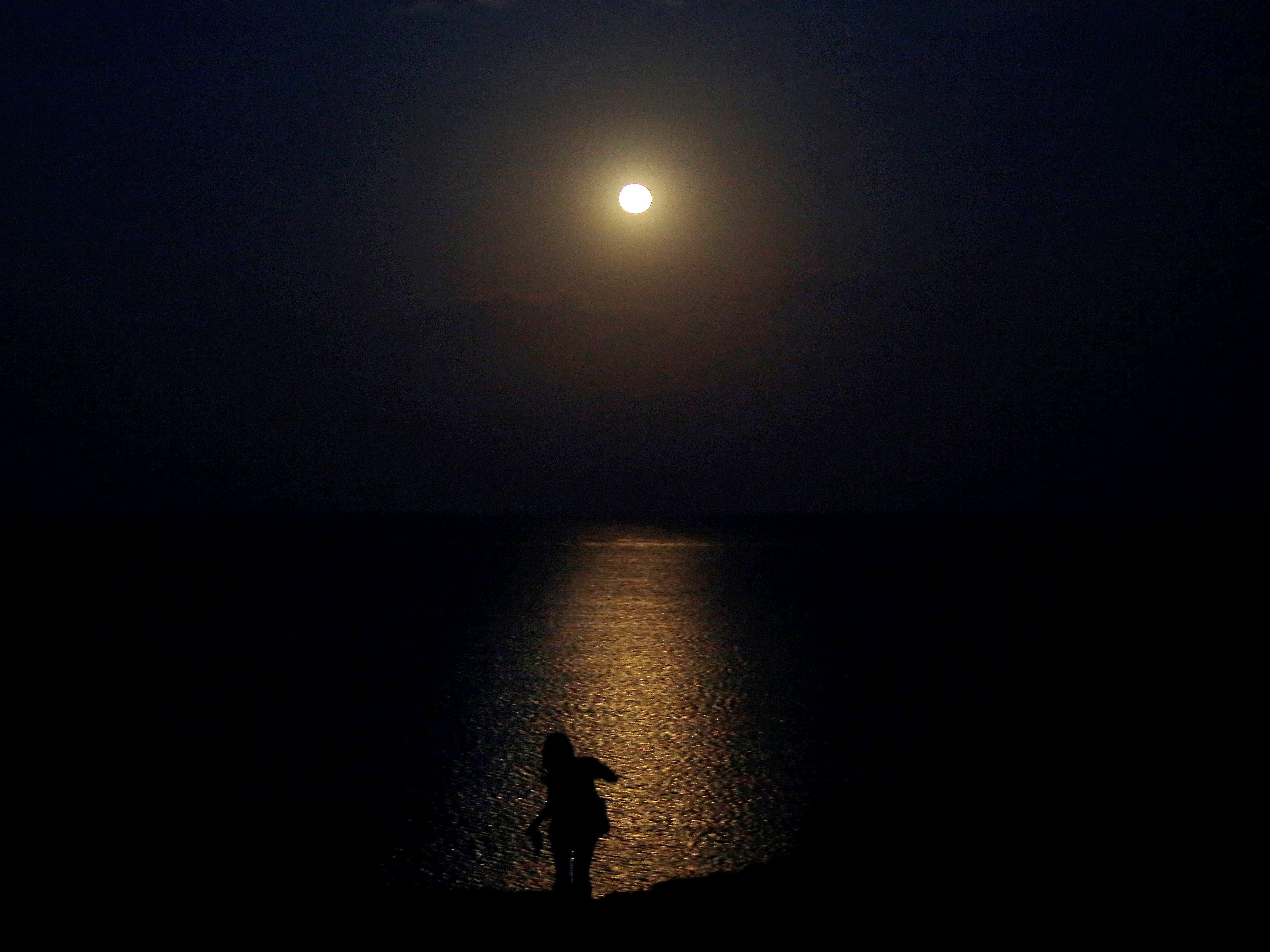 A woman is seen in silhouette against the August full moon light as it rises over the Mediterranean sea in Protaras resort in eastern part of the island of Cyprus, Aug. 26, 2018.