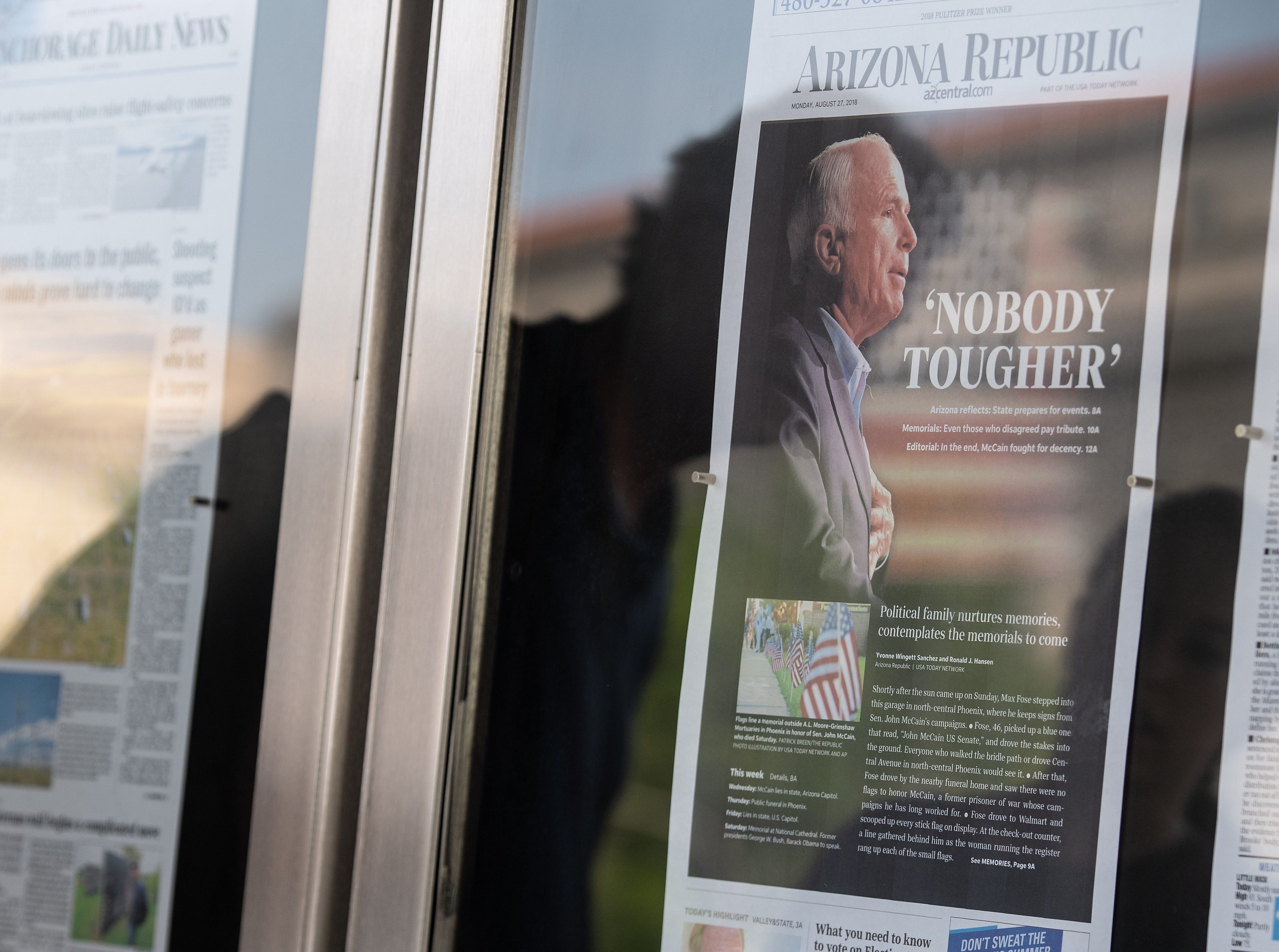 People are reflected as they look at the front page of the Arizona Republic featuring a picture of late Sen. John McCain at the Newseum in Washington, DC, on Aug. 27, 2018. He was a hero, a statesman who cut a towering figure in Washington. But for many in the increasingly angry world of American politics, John McCain will be missed for a far humbler virtue,simple civility. As Americans and others paid tribute to the late Republican senator, who died August 25, 2018 of cancer aged 81, some cited a 2008 interaction with a voter as symbolizing his famous insistence on fair and civil discourse.