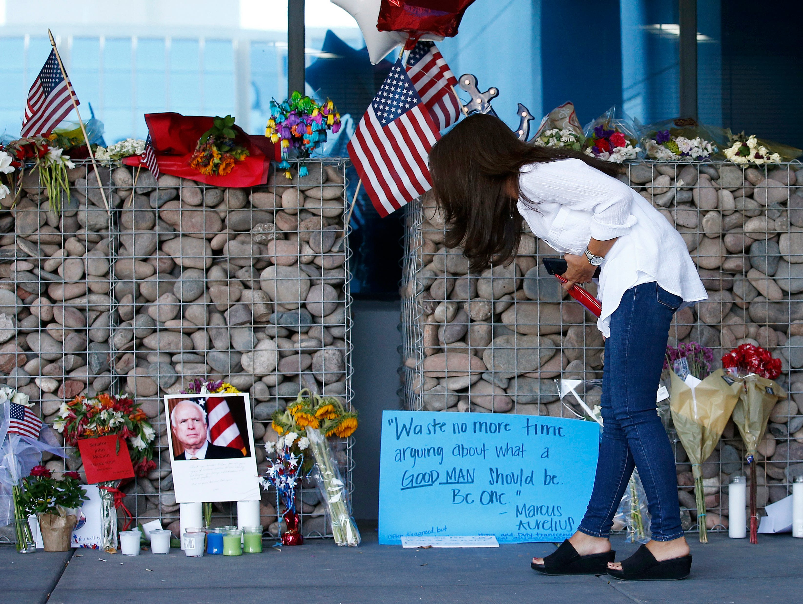 Thu-Van Cunningham, of Phoenix, reads messages left by well-wishers as she visits a makeshift memorial in honor of the late Arizona Republican Sen. John McCain at McCain's office Monday, Aug. 27, 2018, in Phoenix.