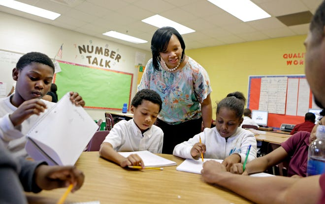 Burgess-Peterson Elementary School principal Robin Robbins, center, meets with students during an after-school study program in Atlanta.