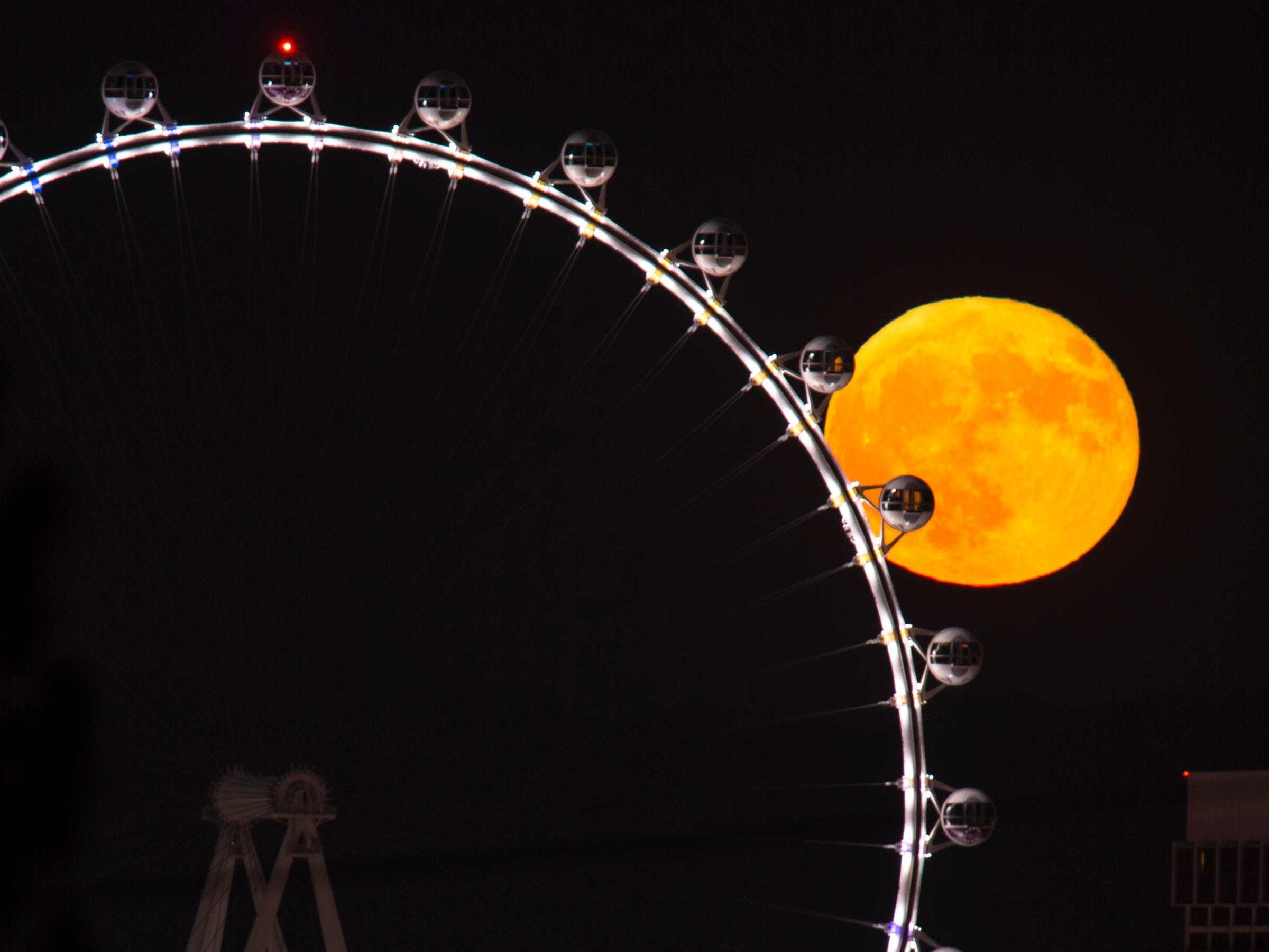 A full moon rises behind the High Roller observation wheel on the Strip in Las Vegas on Sunday, Aug. 26, 2018.
