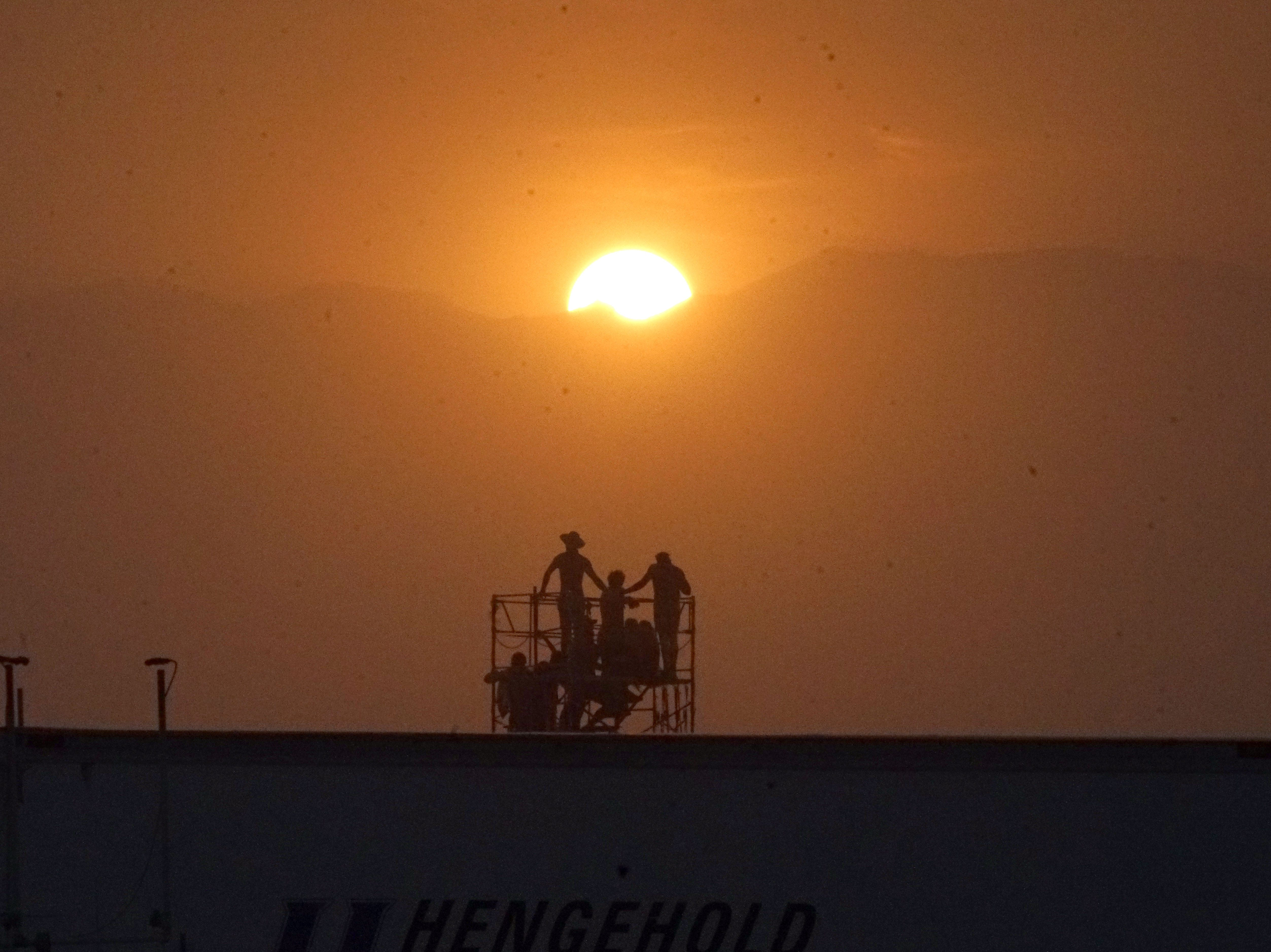 A group of Burning Man attendees watches the setting sun duck behind the mountains on the first official night of Burning Man.