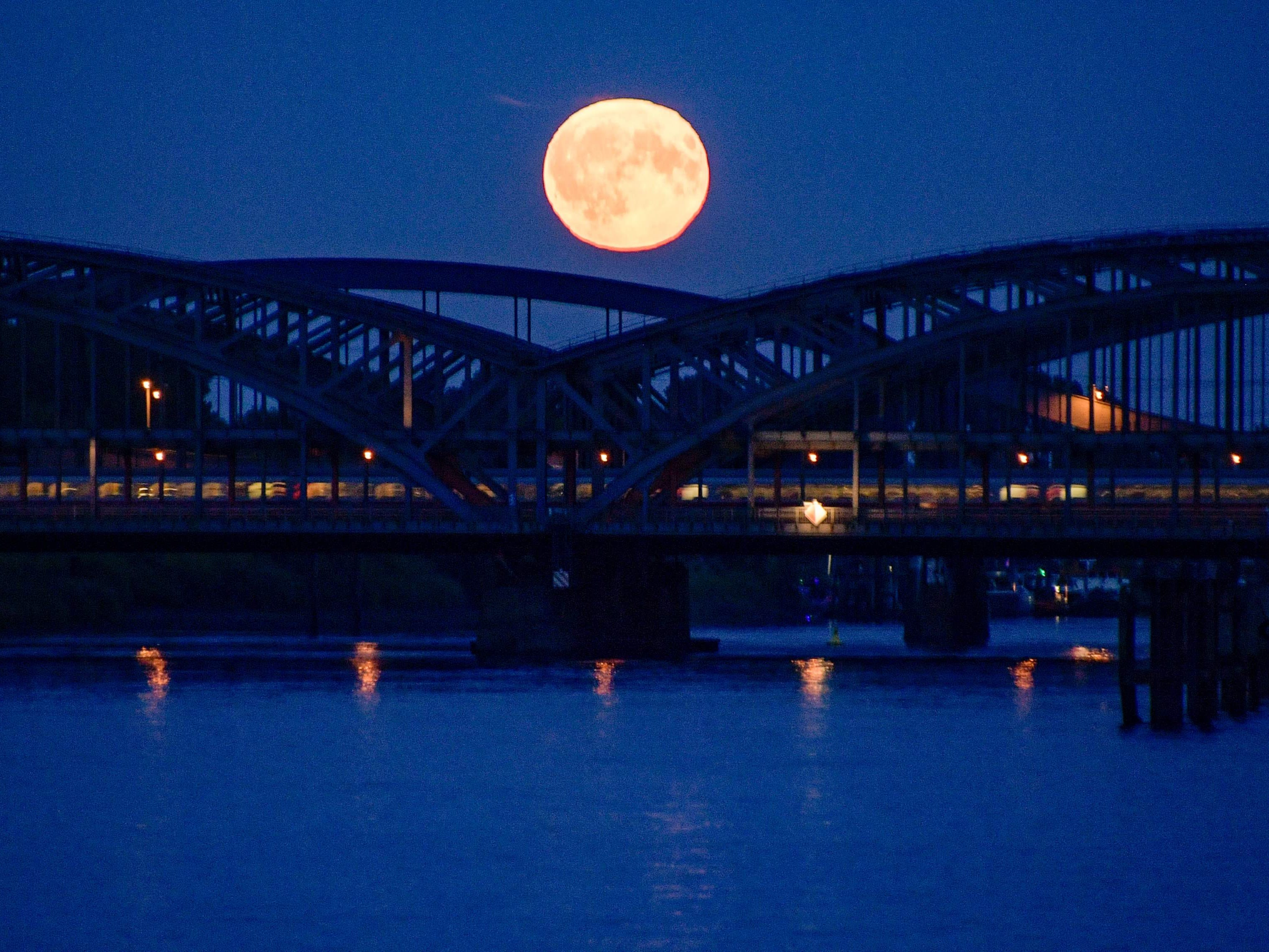 Full moon can be seen on Aug. 26, 2018 behind the Elbbruecken bridges crossing the river Elbe in the Hafencity district of Hamburg, Germany.