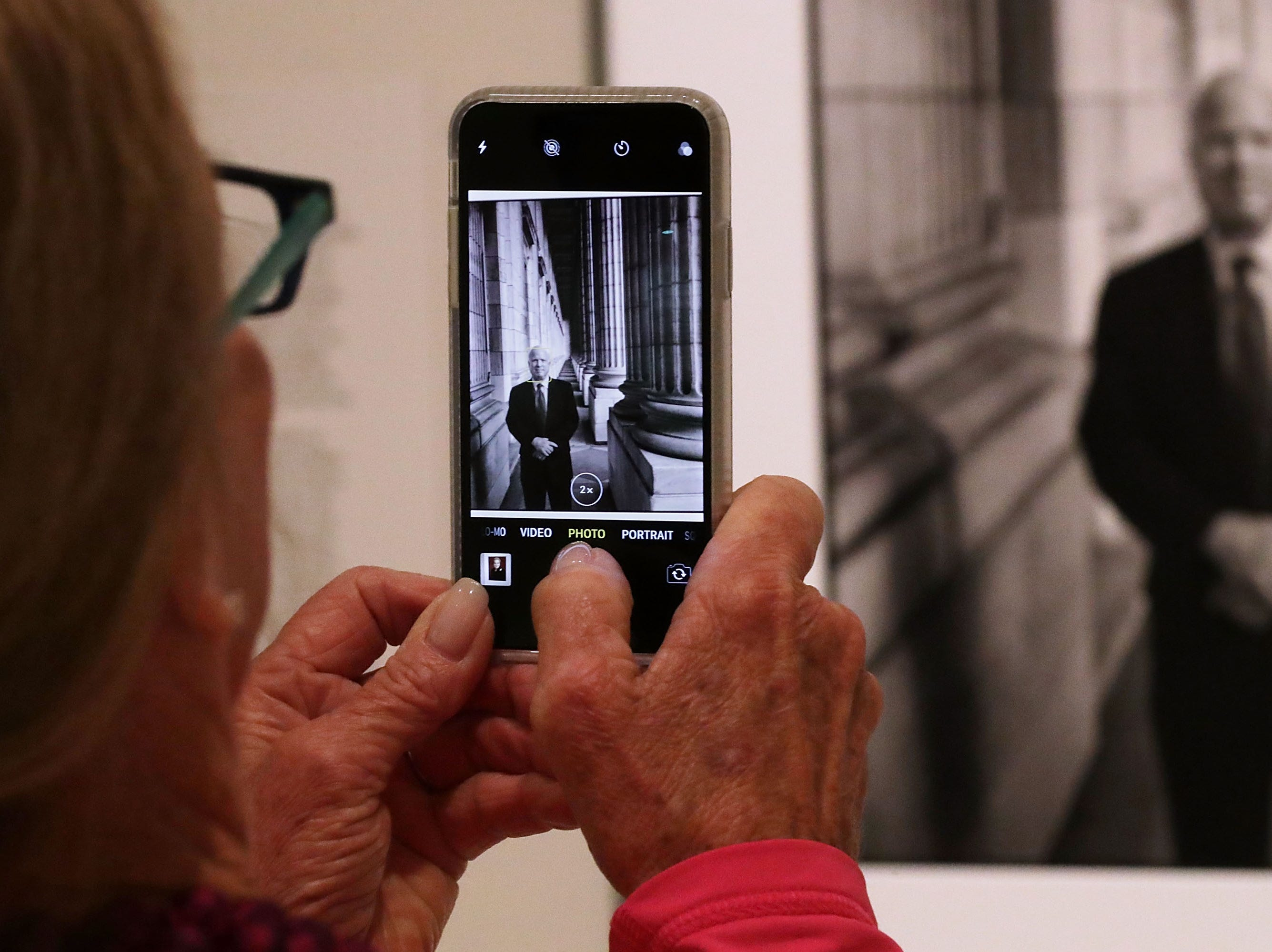A visitor makes a photograph of an image of Sen. John McCain on display at the Smithsonian National Portrait Gallery Aug. 27, 2018 in Washington, DC.