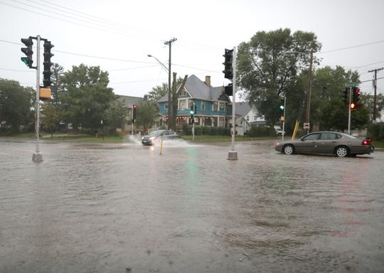 Stormwater floods the intersection of East Wisconsin Avenue and Oak Street in Neenah.