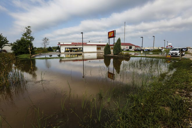 Standing water could be seen Tuesday in many low-lying areas in Fond du Lac after five and a half inches of rain fell in the area over a two-day period. Here, water spills over to the parking lot of Advance Auto Parts on Rolling Meadows Drive.