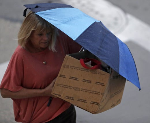 A woman trying to keep her things dry in heavy rain on Tuesday, August 28, 2018 in Green Bay, Wisconsin.