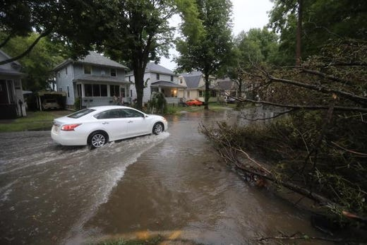 A vehicle rides in Green Bay, Wisconsin on Tuesday, August 28, 2018 after heavy rain fallen tree on the west side of Green Bay over