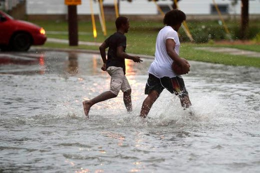 People are crossing a partially flooded Ashland Av e on the west side of Green Bay after heavy rain on Tuesday, August 28, 2018 in Green Bay, Wisconsin.