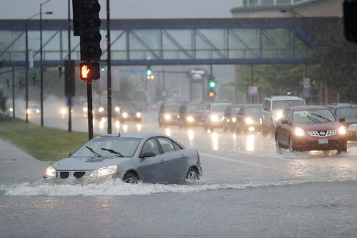 Motorists navigate after a heavy rainfall over a flooded intersection and Madison on Tuesday, August 28, 2018 in Green Bay, Wisconsin