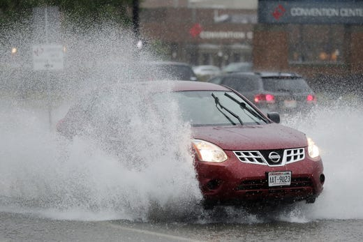 A motorist leaves after heavy rains on Tuesday, the 28th August 2018 in Green Bay, Wisconsin, across a flooded Main Ave.