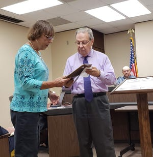 Jan Dukes, Taylor County Tax Assessor Collector, and County Judge Downing Bolls chat as Dukes is awarded a plaque for her years of service to the county.